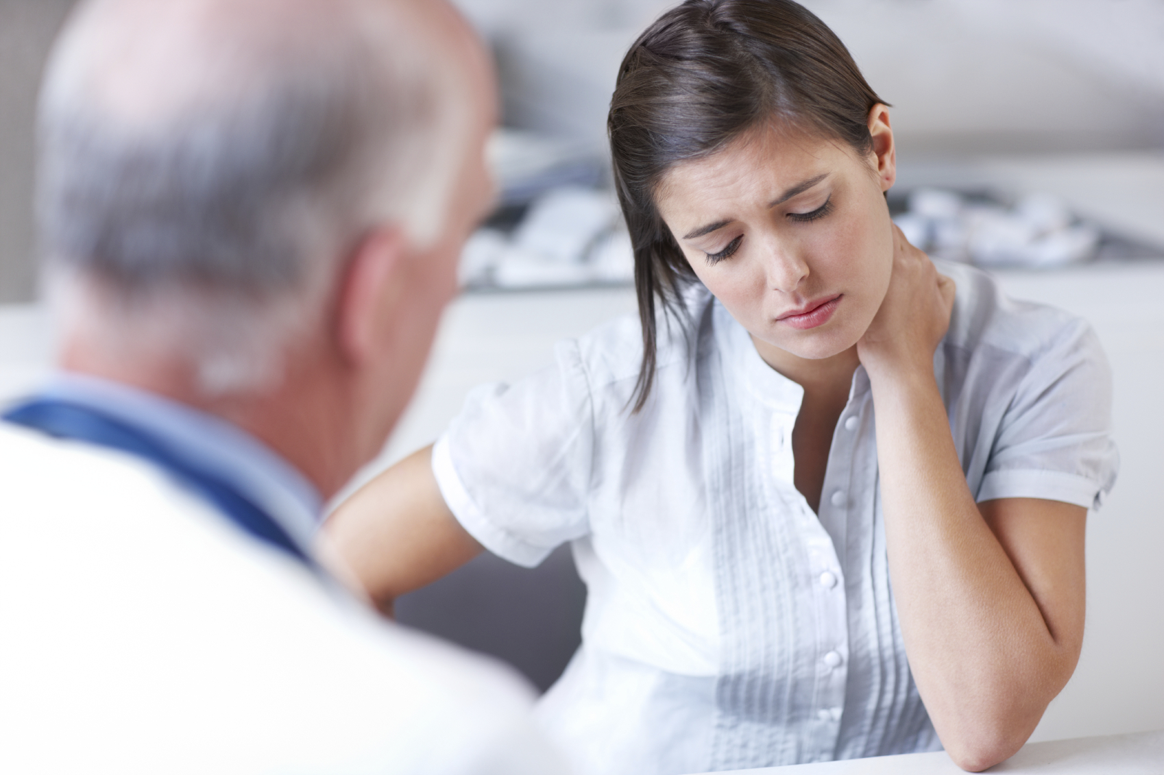 Distraught woman looking down while receiving some upsetting news from her doctor - copyspace